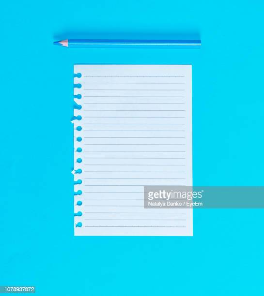 close-up of lined paper and pencil on blue background - lined paper stock pictures, royalty-free photos & images