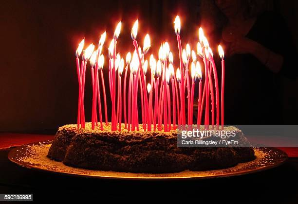 Close-Up Of Lit Birthday Candles On Cake