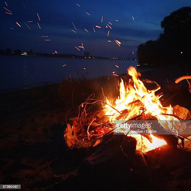 Close-Up Of Lit Bonfire On Beach Against Sky At Night