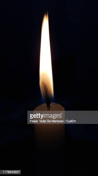 close-up of lit candle against black background - brazilian waxing stock photos and pictures