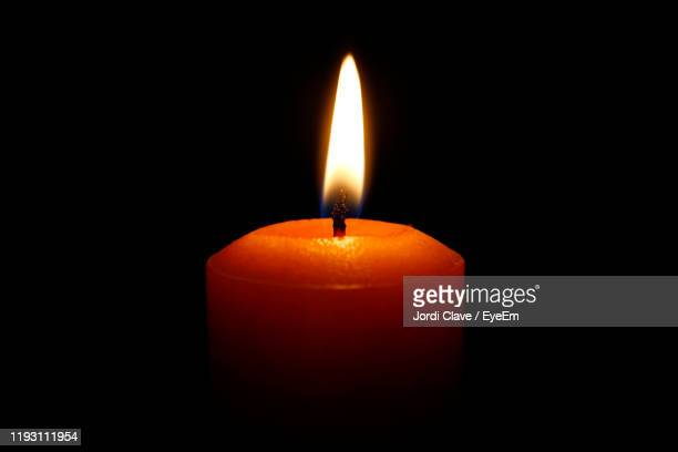 close-up of lit candle against black background - candlelight stock pictures, royalty-free photos & images