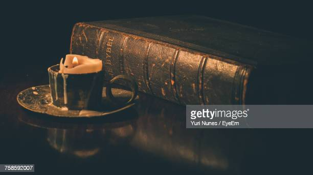 Close-Up Of Lit Candle And Bible In Darkroom