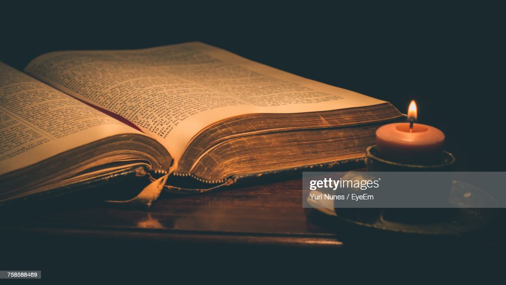 Close-Up Of Lit Candle And Bible On Table In Darkroom : Stock Photo
