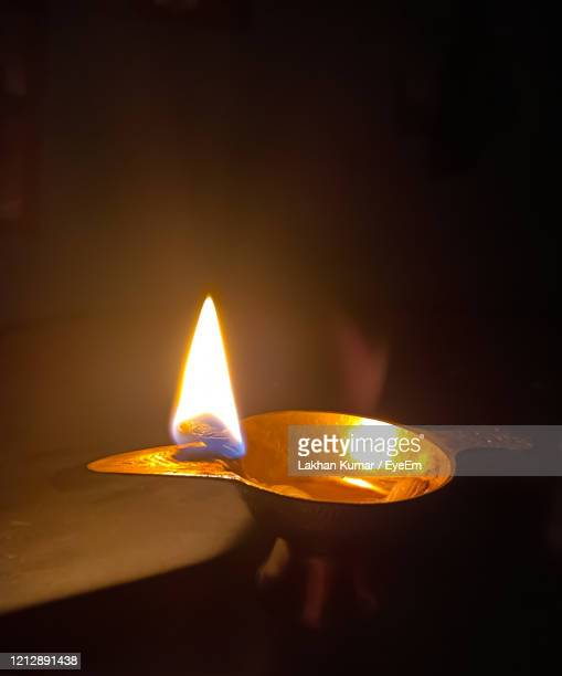 close-up of lit candle in the dark - candle in the dark stock pictures, royalty-free photos & images