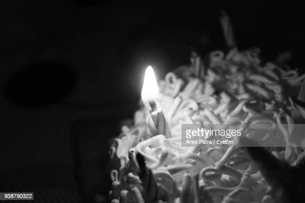 Close-Up Of Lit Candle On Cake In Darkroom