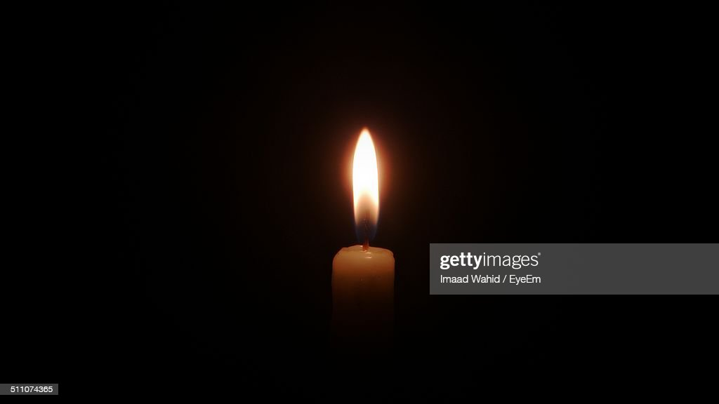 Close-up of lit candle over black background : Stock Photo