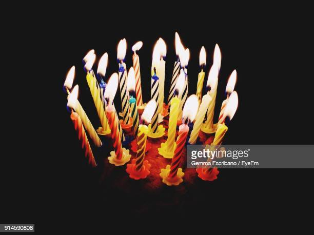 close-up of lit candles against black background - birthday cake lots of candles stock photos and pictures