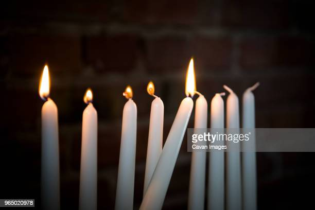close-up of lit candles in darkroom against brick wall during hanukkah - hanukkah stockfoto's en -beelden