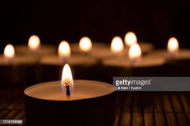 close-up of lit candles in darkroom - candle stock pictures, royalty-free photos & images