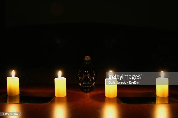 close-up of lit candles in the dark room - candle in the dark imagens e fotografias de stock