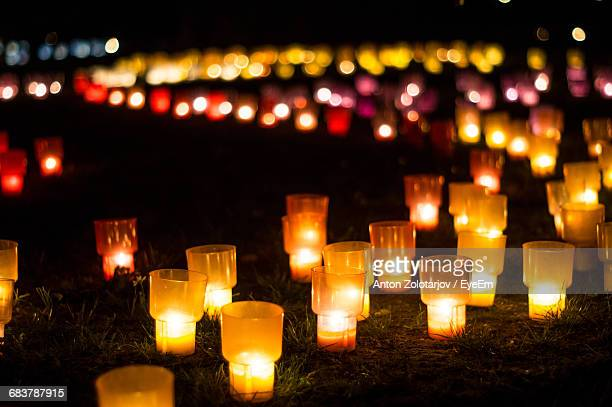 Close-Up Of Lit Candles On A Field At Night