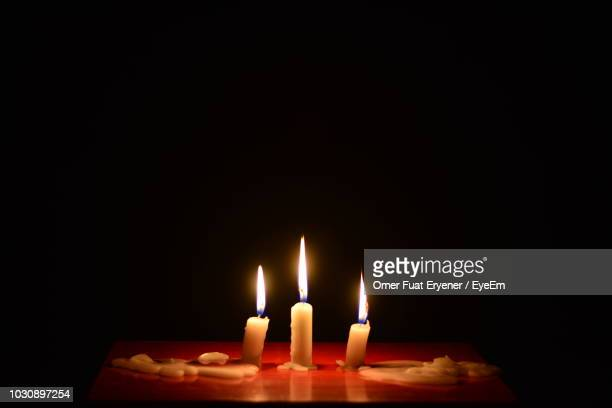 close-up of lit candles on table in darkroom - bougie photos et images de collection