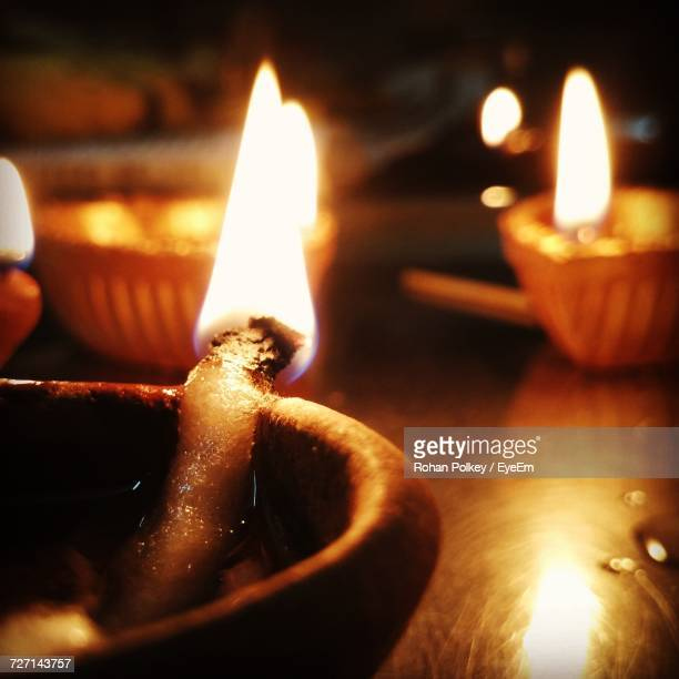 Close-Up Of Lit Candles On Table