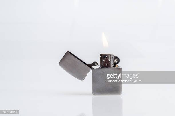 close-up of lit cigarette lighter against white background - cigarette lighter stock pictures, royalty-free photos & images