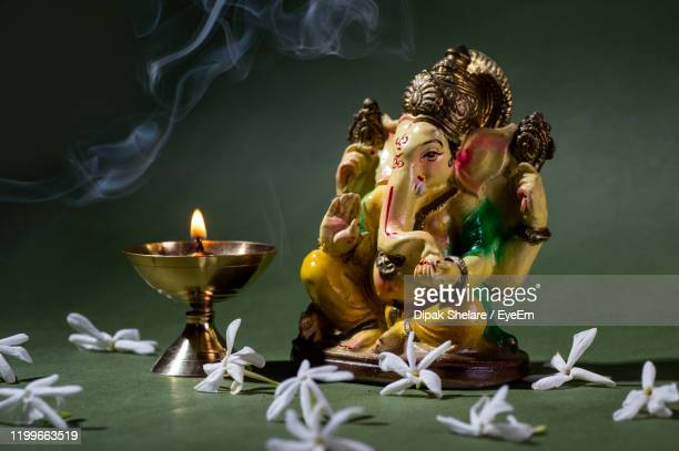 close-up of lit diya by ganesha idol and flowers - ganesha stock pictures, royalty-free photos & images