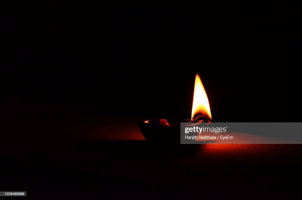 Close-Up Of Lit Diya On Table In Darkroom : Stock Photo