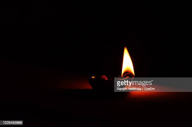 close-up of lit diya on table in darkroom - diya oil lamp stock pictures, royalty-free photos & images