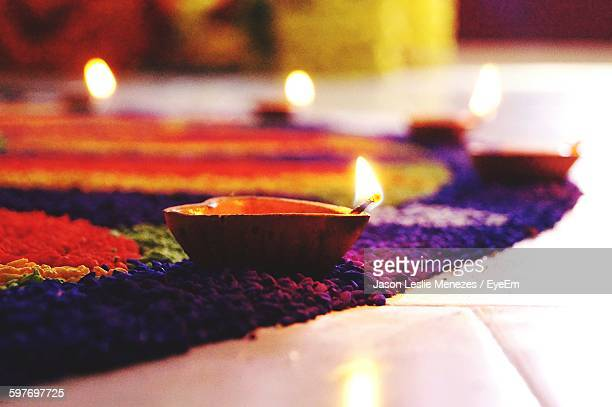 Close-Up Of Lit Diyas On Rangoli At Home