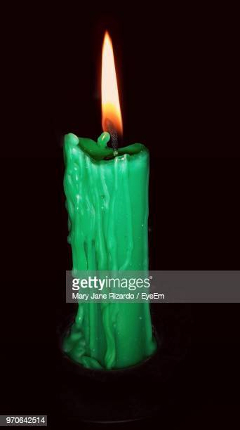 close-up of lit green candle over black background - mary moody fotografías e imágenes de stock