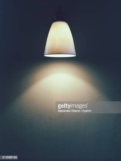 Close-up of lit lamp against the wall