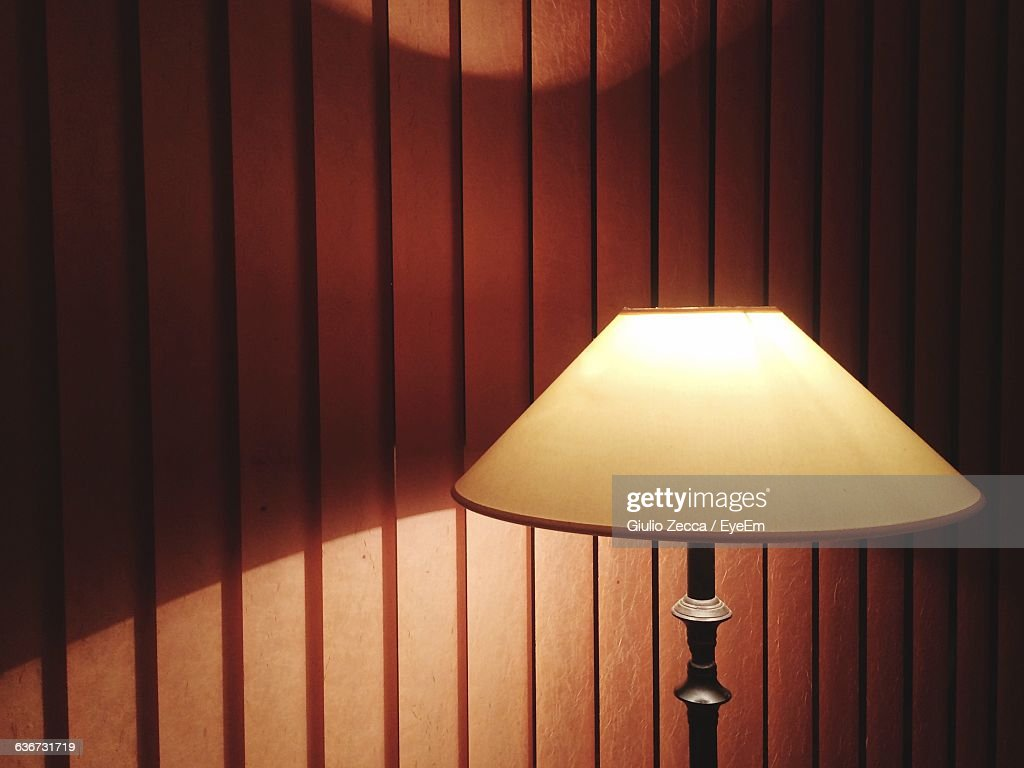 Close-Up Of Lit Lamp Against The Wall : Stock Photo