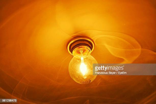 Close-Up Of Lit Light Bulb At Ceiling