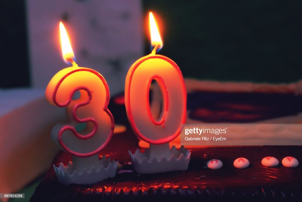 Closeup Of Lit Number Candles On Birthday Cake At Home Stock Photo