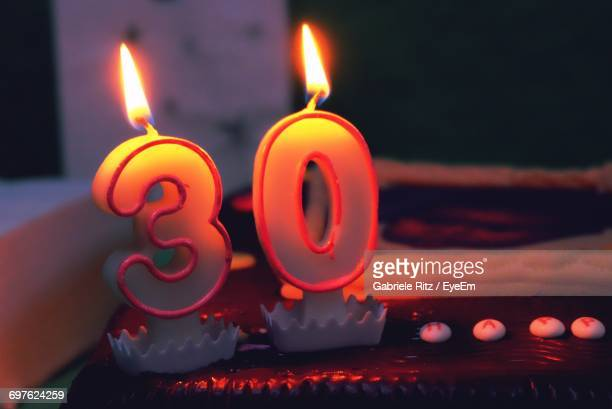 Close-Up Of Lit Number Candles On Birthday Cake At Home