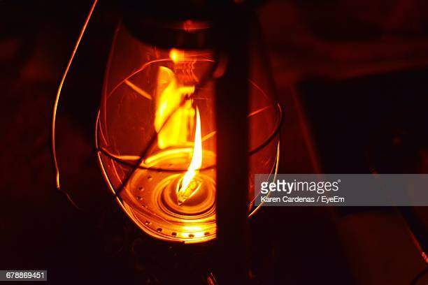 close-up of lit oil lantern in darkroom - oil lamp stock pictures, royalty-free photos & images