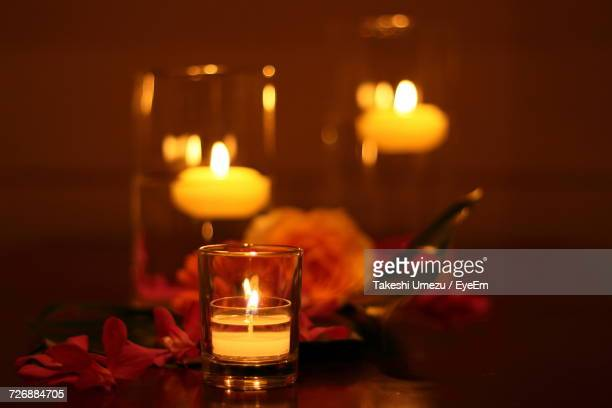 close-up of lit tea light candle in glass on table - ローソク ストックフォトと画像