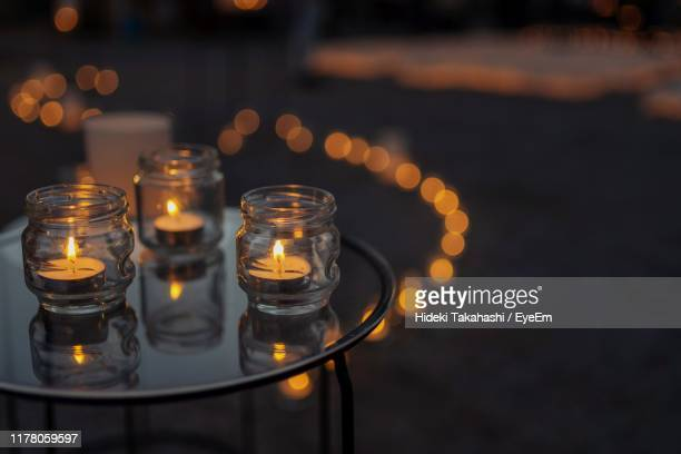 close-up of lit tea light candles on table - jar stock pictures, royalty-free photos & images