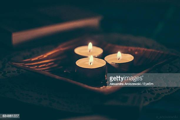 Close-Up Of Lit Tea Light Candles On Table