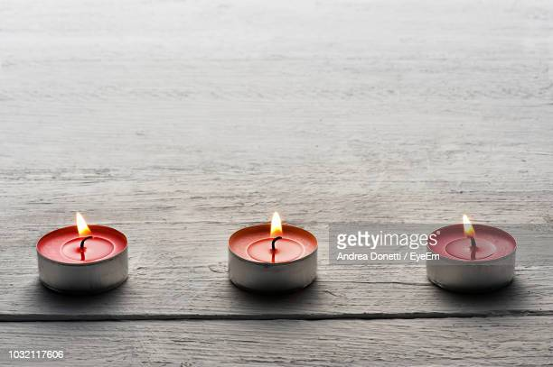 Close-Up Of Lit Tea Light Candles On Wooden Table