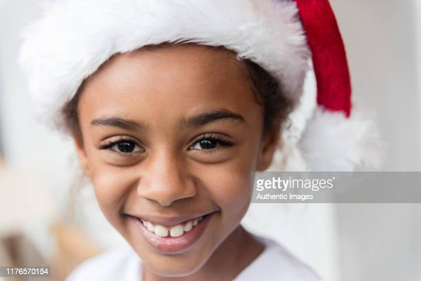 close-up of little black girl with big smile and christmas hat - santa close up stock pictures, royalty-free photos & images
