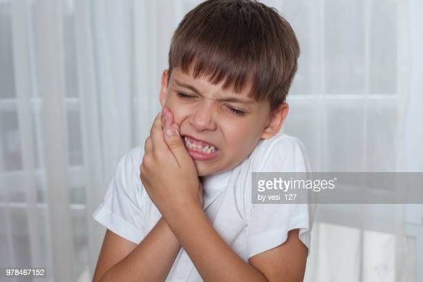 Close-up of little boy having toothache