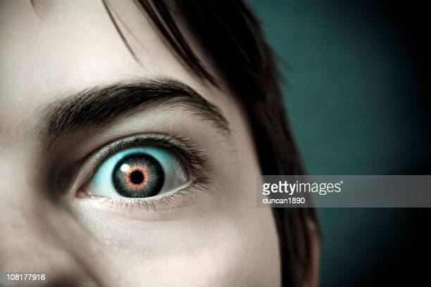 close-up of little boy's eye with red pupil - magic eye stock pictures, royalty-free photos & images