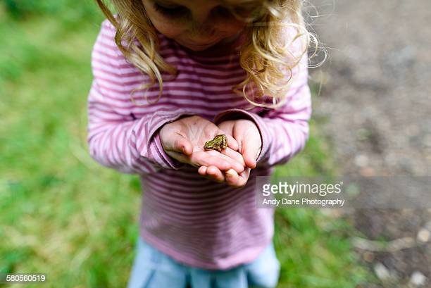 Closeup of little girl holding small frog