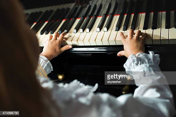 Close-up of little girl playing the piano.