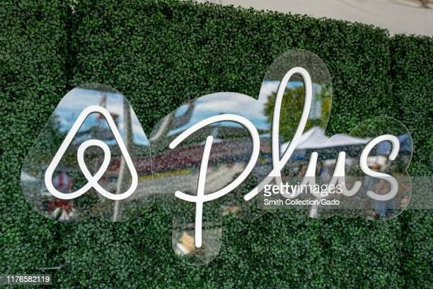 Close-up of logo for AirBNB Plus, a division of sharing economy vacation rental company AirBNB focusing on higher-end homes, against a green wall in...
