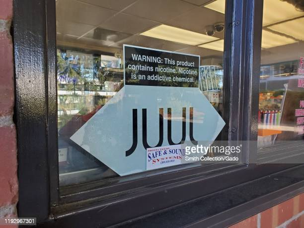 Close-up of logo for e-cigarette or vape company Juul on glass window of convenience store in San Ramon, California, December 6, 2019.