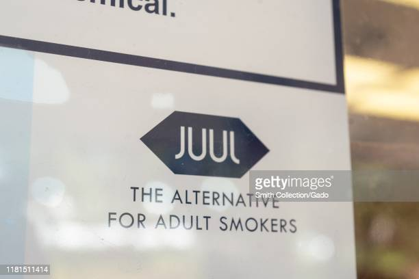 Close-up of logo for electronic cigarette or vaping company Juul, with tagline The Alternative for Adult Smokers visible, on window advertisement in...