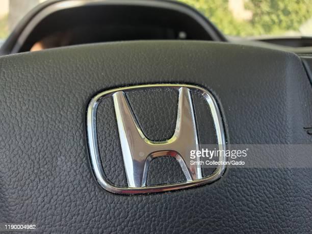 Close-up of logo for Honda automobile company on steering wheel of Honda CRV SUV, Danville, California, August 13, 2019.