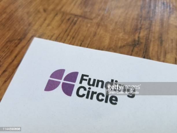 Close-up of logo for peer-to-peer lending company Funding Circle on paper, against a light wooden surface, April 21, 2019.
