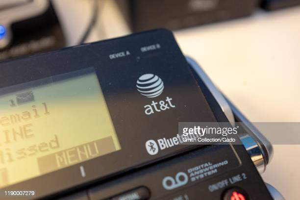 Close-up of logo for telecommunications company ATT on a desktop phone in an office, with Bluetooth logo also visible, August 21, 2019.