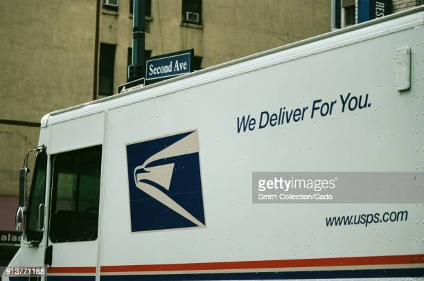 Closeup of logo on a United States Postal Service mail truck with tagline reading 'We Deliver For You' driving down 2nd Avenue in Manhattan New York...