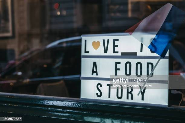 close-up of love is a food story sign in the window of a restaurant. - western script stock pictures, royalty-free photos & images