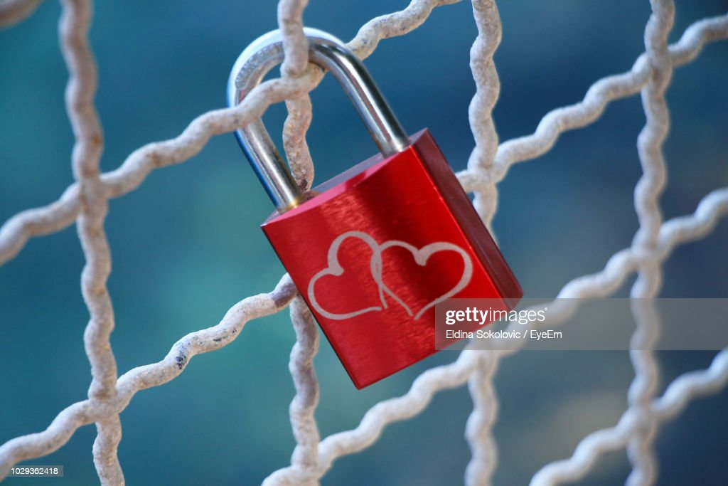Close-Up Of Love Lock Hanging On Metal Grate : Stock Photo