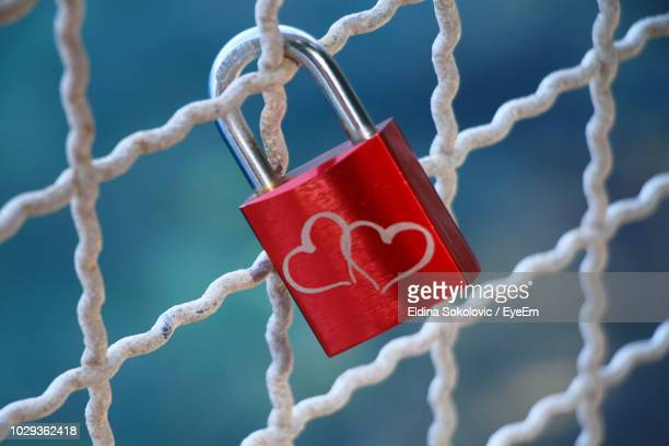 close-up of love lock hanging on metal grate - metal grate stock photos and pictures