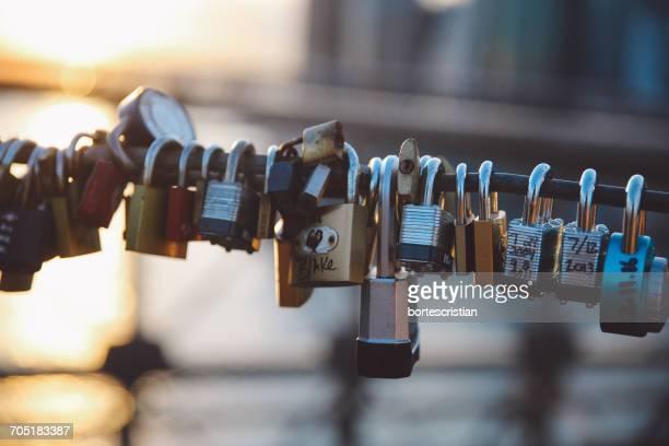 close-up of love locks hanging on railing at brooklyn bridge - bortes foto e immagini stock