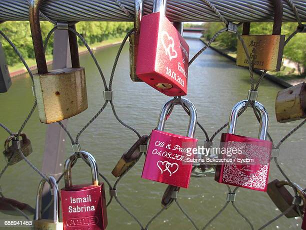 Close-Up Of Love Locks On Railing On Bridge Over River